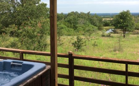 Hot tub on deck with view of ranch
